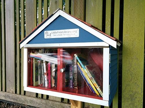 Little Free Library shaped like a blue house