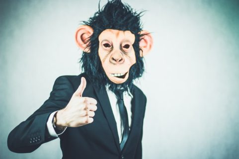 man in monkey mask giving thumbs up