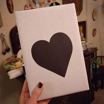 wrapped book with a black heart on the front